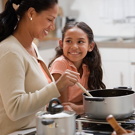 Mother teaching daughter the importance of cooking and eating vegetables with everyday meals.