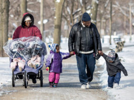 African American Family Walking in Winter Snow During Holiday Season